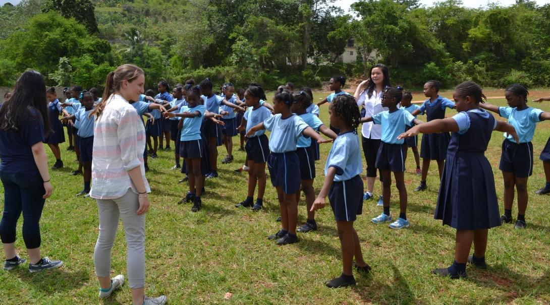 As part of the Public Health placement for teenagers in Jamaica, students have fun with school children during an exercise activity.